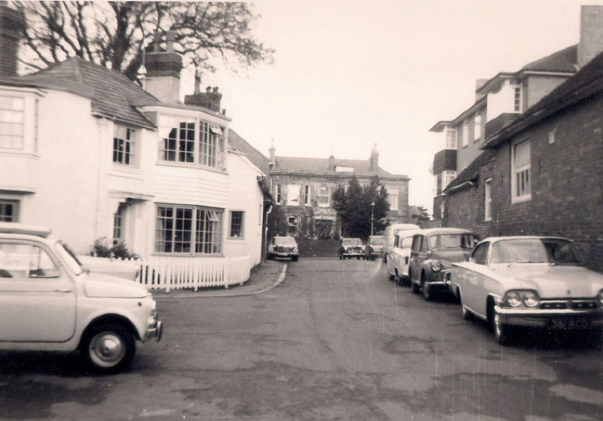 the High Street in the background, this lane housed the doctor's surgery and the village hall - Love the Cars!!