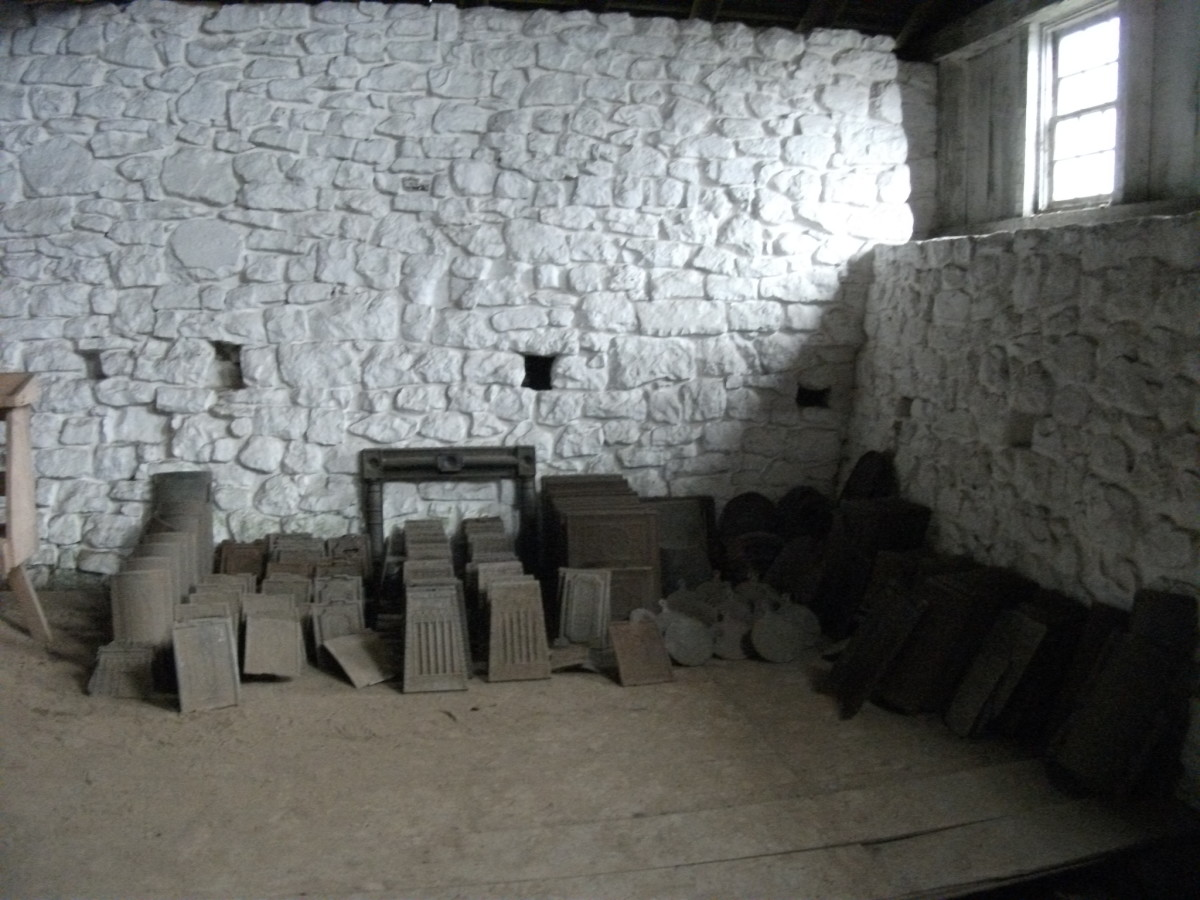 Iron stove parts stacked in the casting house of Hopewell Furnace.