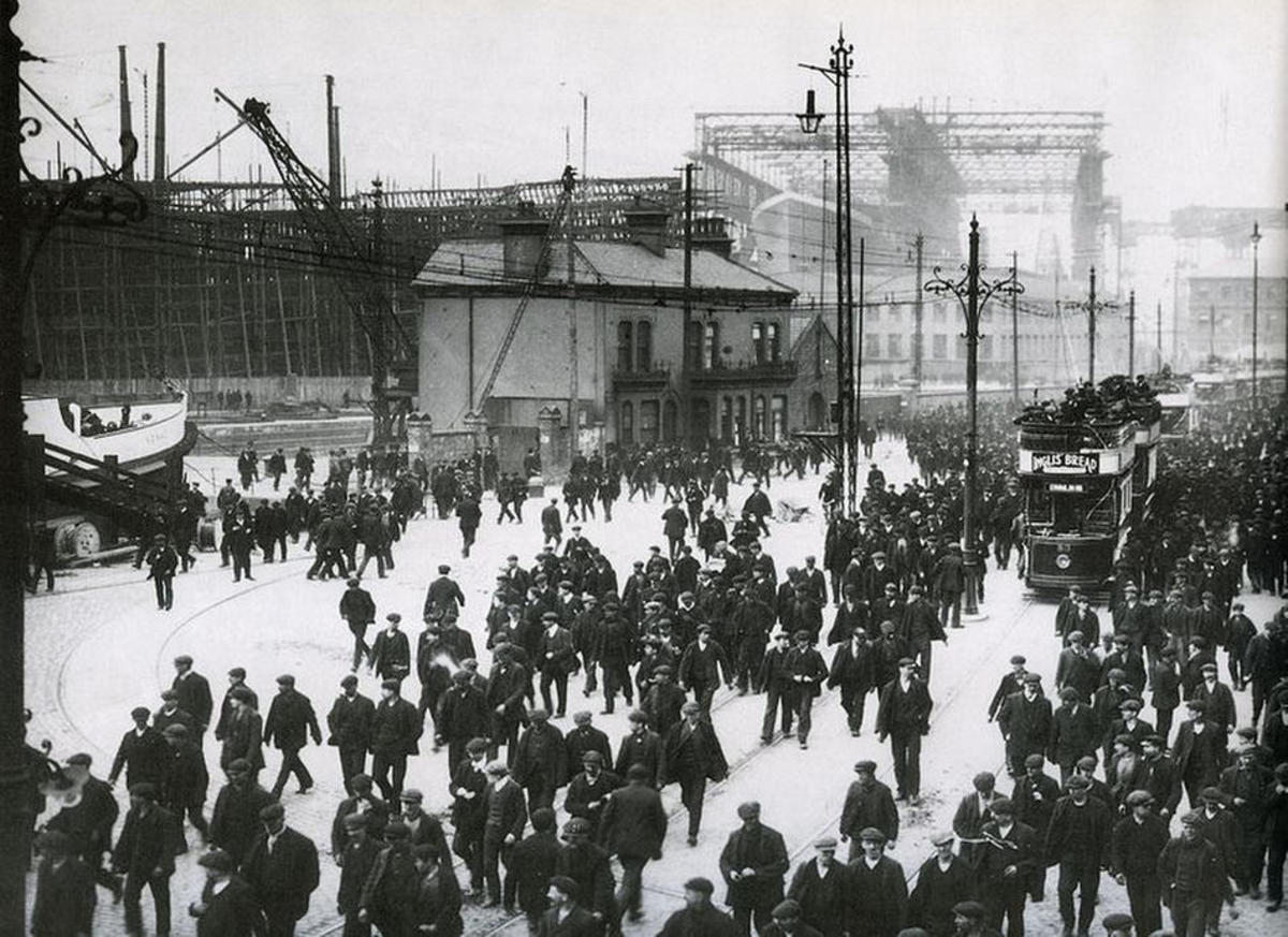 End of shift for workers at Harland and Wolff with Titanic on the stocks behind