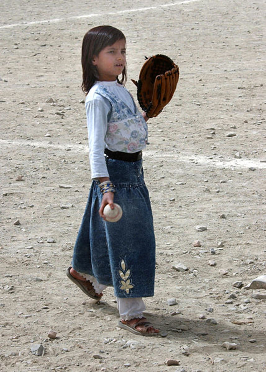An Afghan girl plays with her baseball and glove at Camp Harriman.