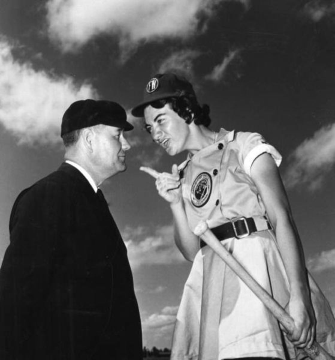 Fort Wayne Daisies player, Marie Wegman, of the All American Girls Professional Baseball League and umpire Norris Ward. April 1948.