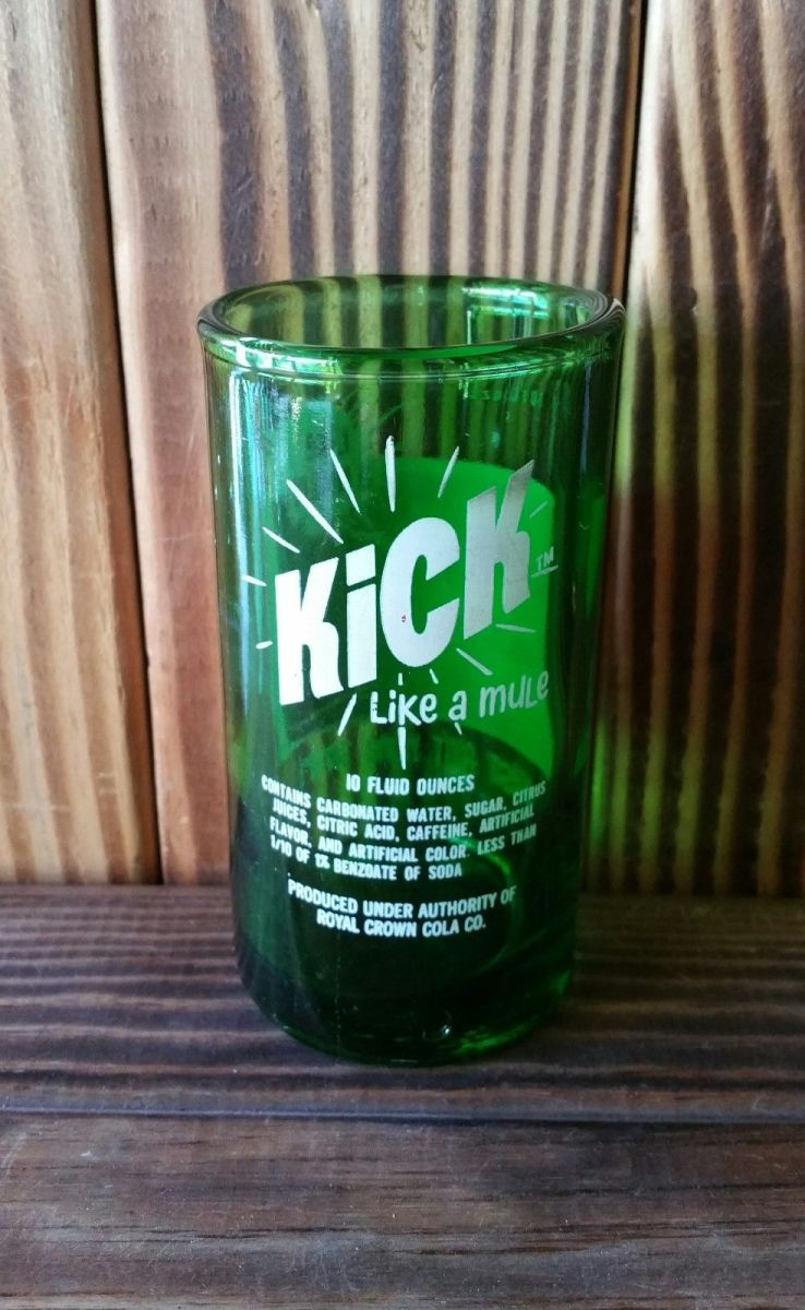 The back side of the Yava Glass, this is an Up-cycled Kick Like a Mule Soda Bottle Glass 4.5 inches tall, holds 6 fluid ounces, green glass with multi colored screen print