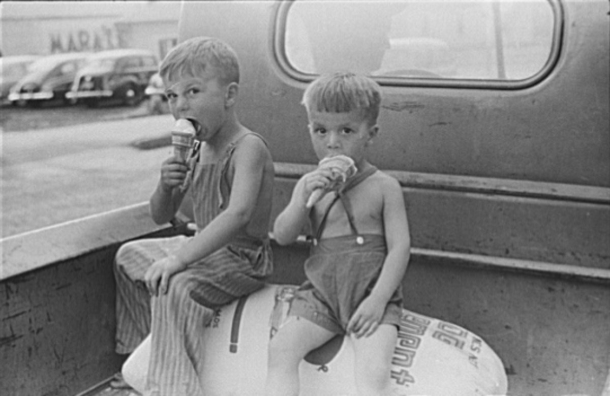 """Farm boys eating ice-cream cones. Washington, Indiana"" 1941. Two boys seated on sacks in back of pickup-truck eating ice-cream."