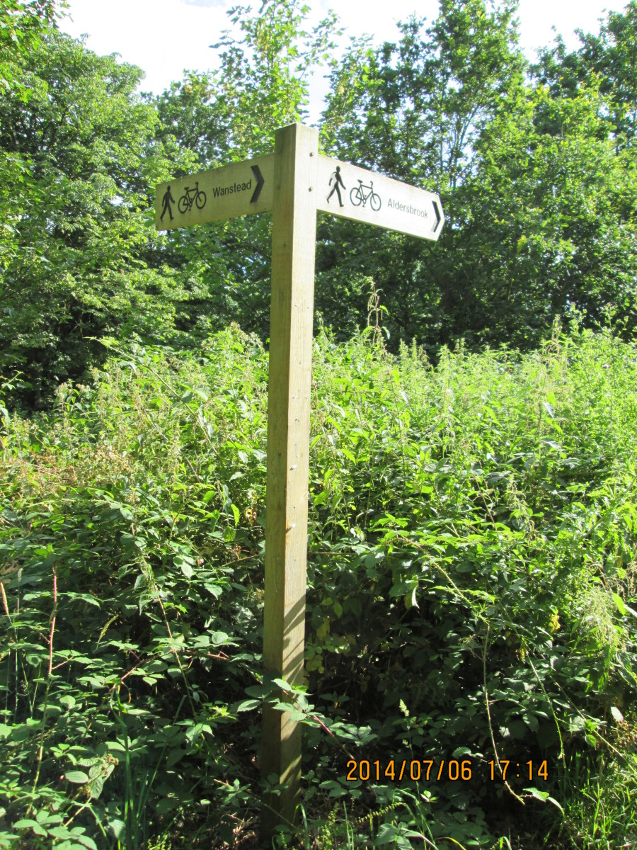 Cycle track signpost erected before 2012 London Olympics points one way to Wanstead, the other to Stratford via Aldersbrook