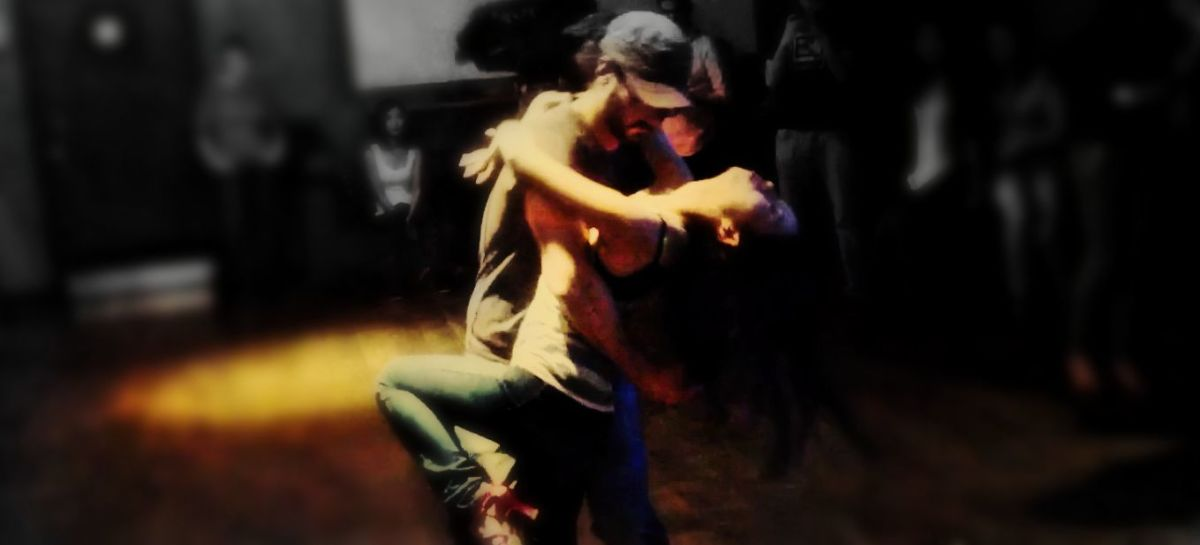 Couple dancing bachata together, with the woman wearing skinny jeans