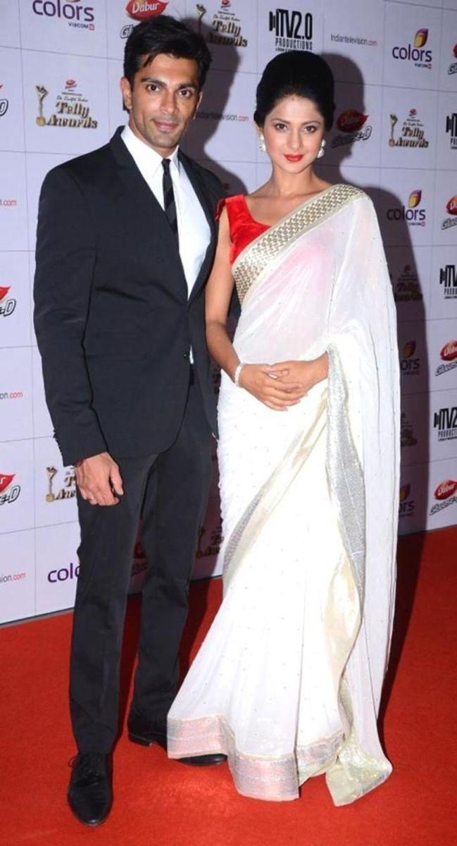 White chiffon saree with red sleeveless saree blouse.