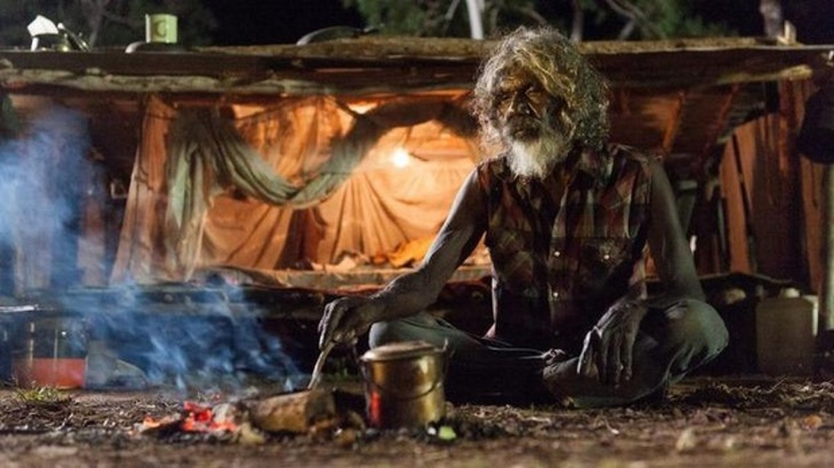 Aboriginal man boiling a billy and cooking on a campfire