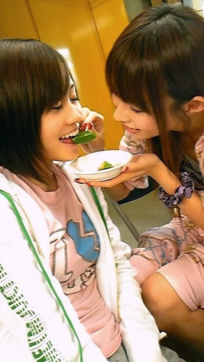 This is so cute! Atsuko Maeda (left) is being fed cucumber by Megumi Ohori. The picture shows that she is more than enthusiastic about the situation. Megumi Ohori is pictured on the right.