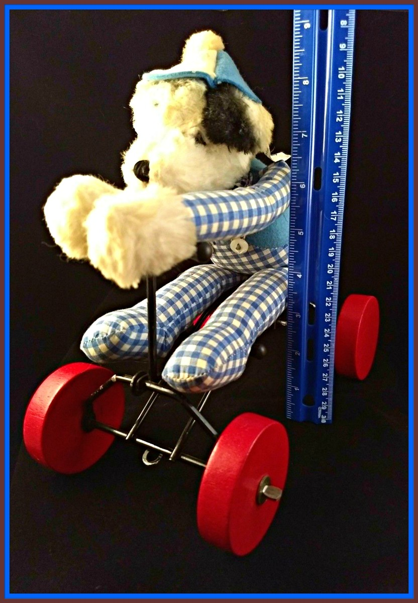 The dog looks like a Dalmatian (he has spots) and black and white ears.  He has a red felt tongue and embroidered black mouth and nose.   He is wearing blue and white checkered overalls, and a blue felt shirt with blue and white checkered sleeves.