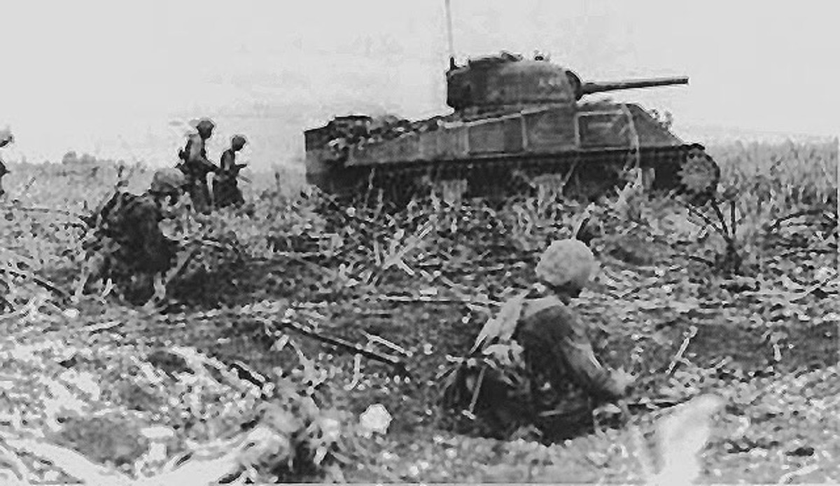 A Marine tank-infantry team advances during the Battle for Tinian.