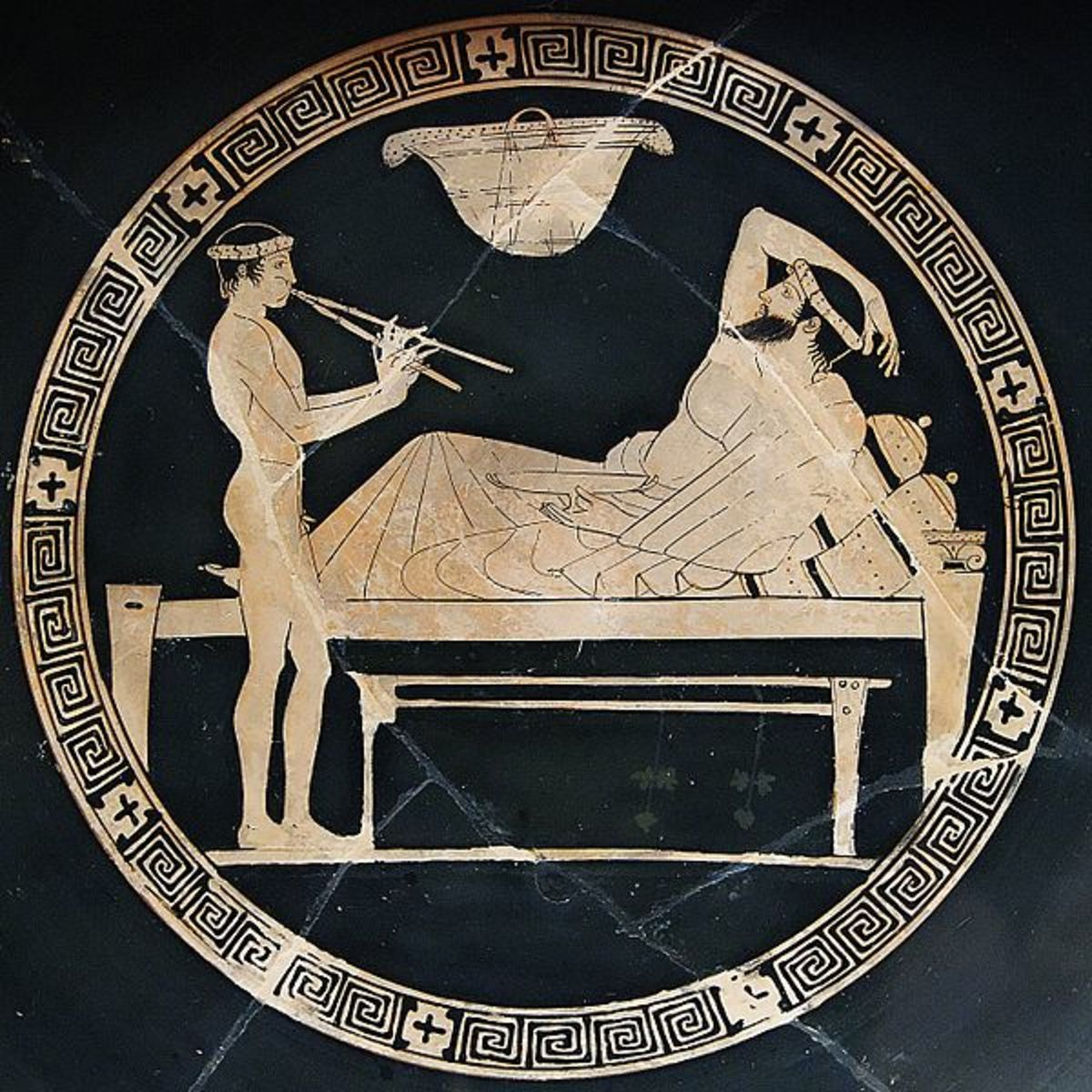 Banquet scene: man reclining on a bench and youth playing the aulos. Tondo of an Attic red-figure cup, ca. 460 BC–450 BC.