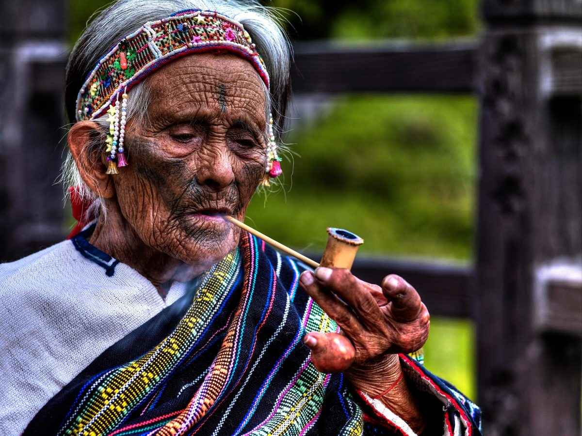 Elderly member of the Atayal tribe smoking a pike.  Facial tattooing is one of the most important customs of this tribe - a custom which dates back over 1,400 years.  They are used to indicate one's place within the tribe.