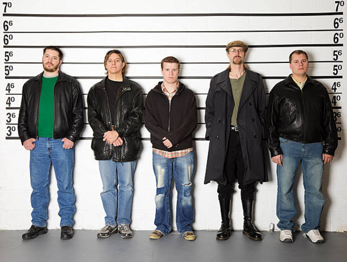 We're all lined up, as different as Goofy and Clint Eastwood. The old biddy coughs and beckons the officer in charge...
