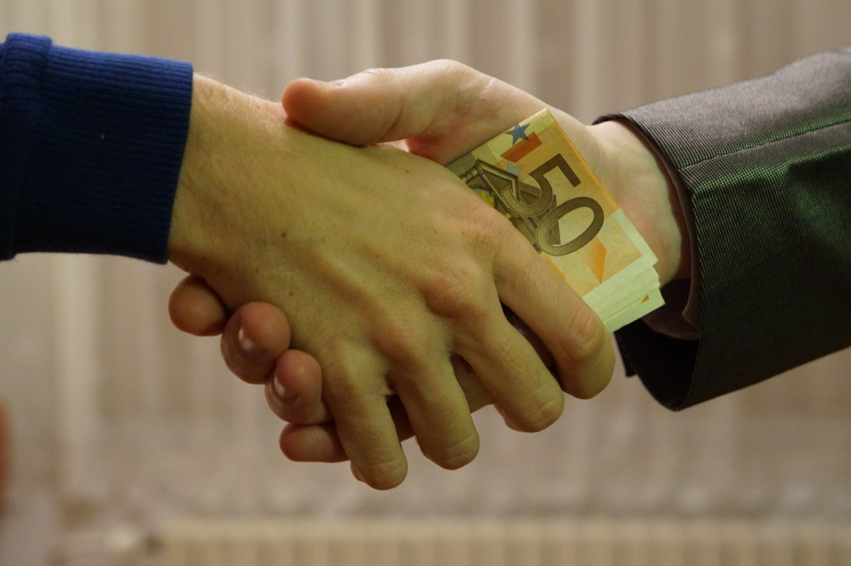 Hand shaking with euros (this a method of giving out bribe)