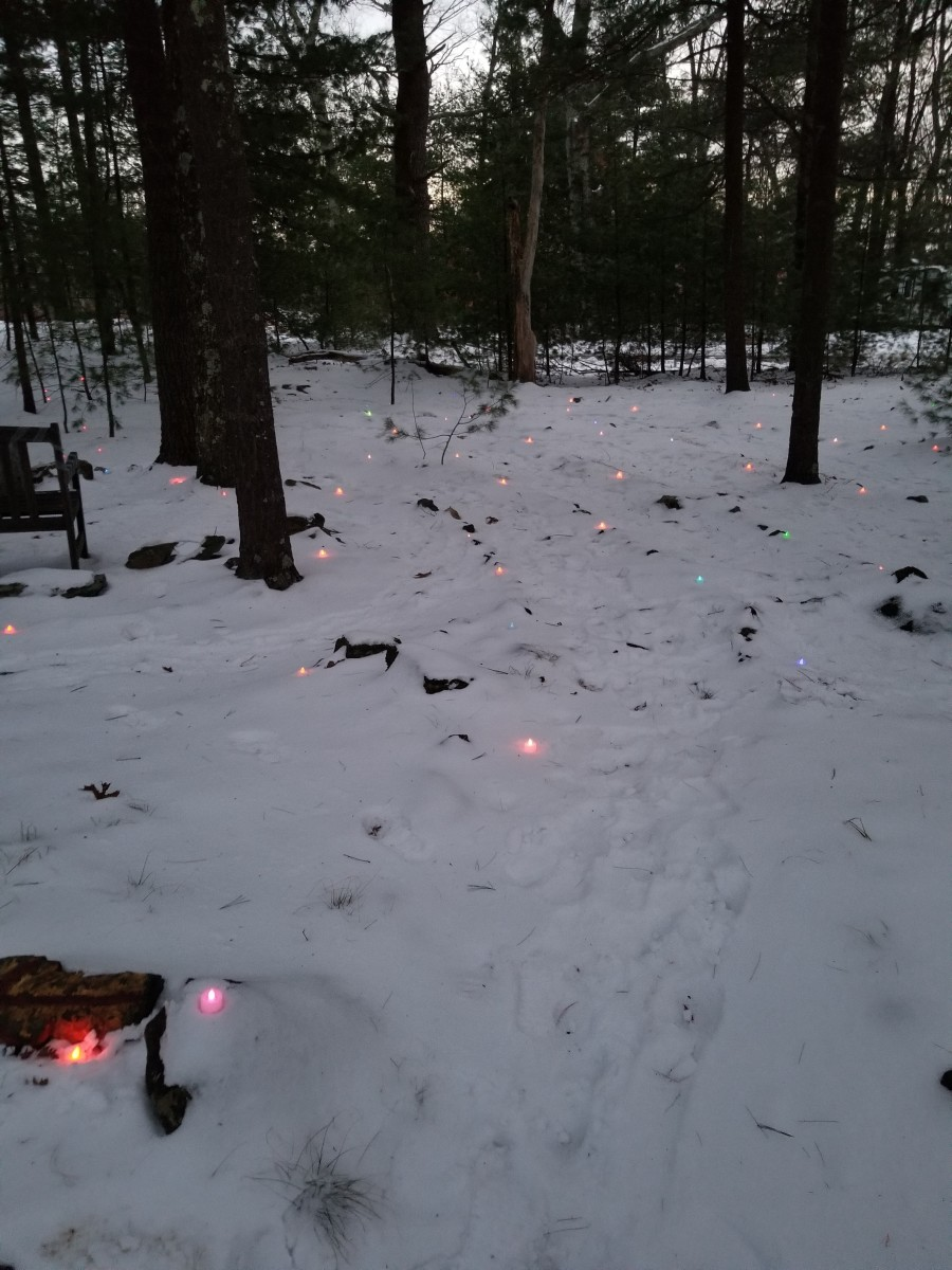 Footprints on the snowy wooded labyrinth path lit with rainbow lights for the Winter Solstice in New England.  Dusk is a magical time to walk a labyrinth.  It is the time of transition between afternoon and evening.