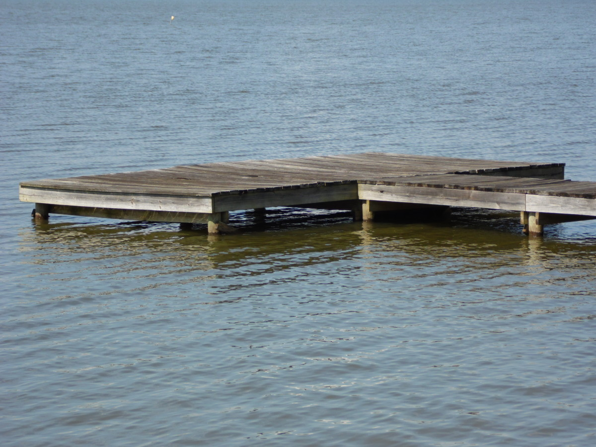 Simple dock sits alone in the water.