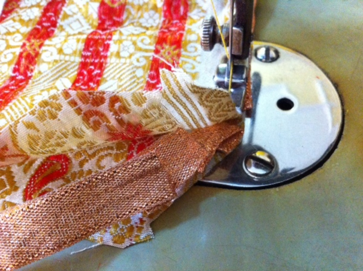 Keep the ribbon in between while sewing and fold it at some places to give a round shape