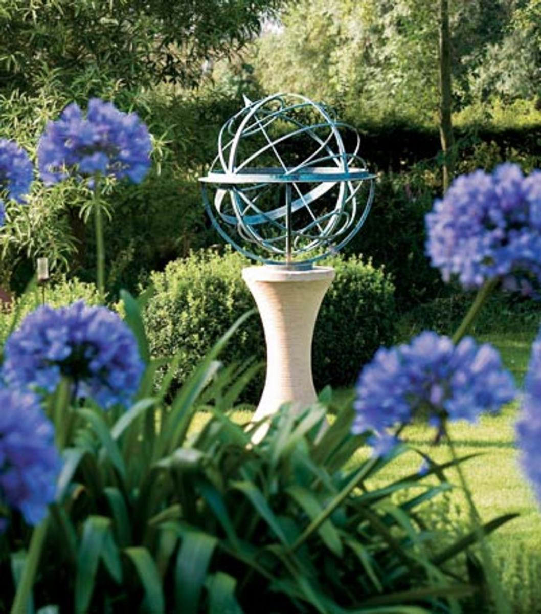 This is another cool, modern landscape ornament. It's eye catching design draws attention and it's rounded shape is mirrored in the round, purple flower blooms of the bushes around it.
