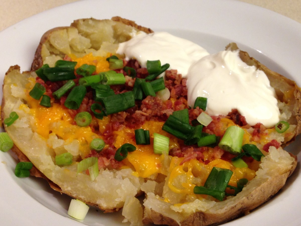 Loaded baked potato with butter, sour cream, cheese, bacon bits, and scallions
