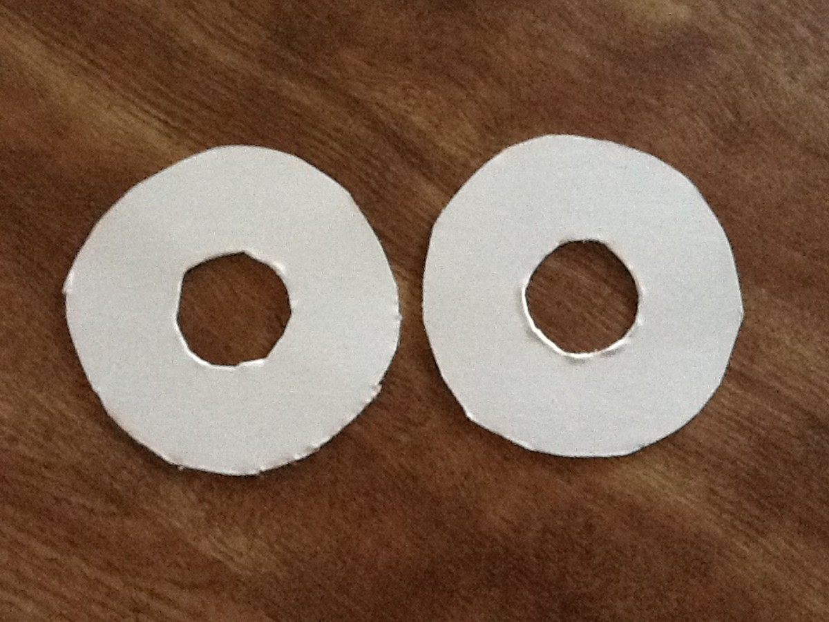 Cut out 2 circles from cardboard. Cut 2 circles from center to make a doughnut. The size of the circle will depend on how big a pom pom you want. I used a drinking glass for thew outside circle, for the inside I used a bottle cap.