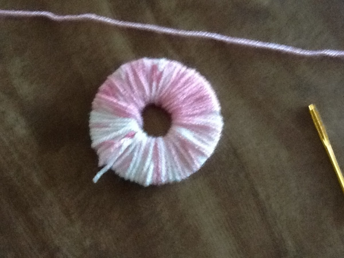 Completely cover the doughnut with the yarn. The more yarn you use the fuller your pom pom will be.