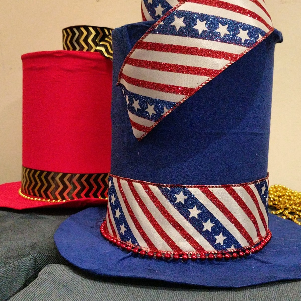Hats post fabric, ribbon bands, and Mardi Gras beads.