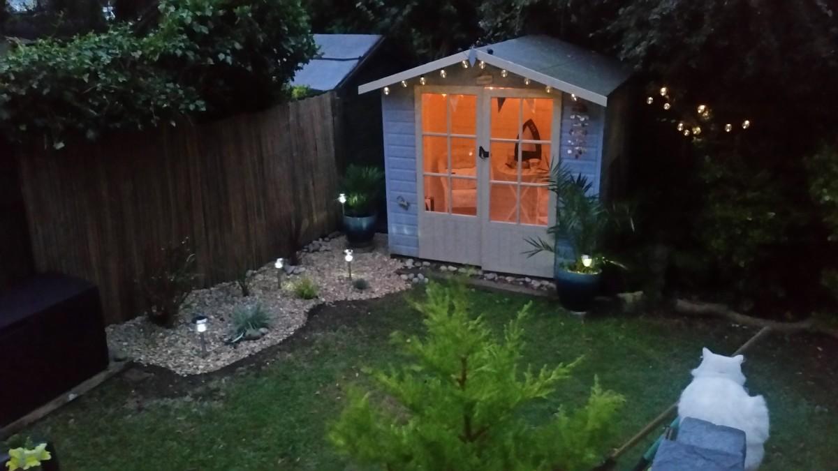 Beach hut themed garden room at night.