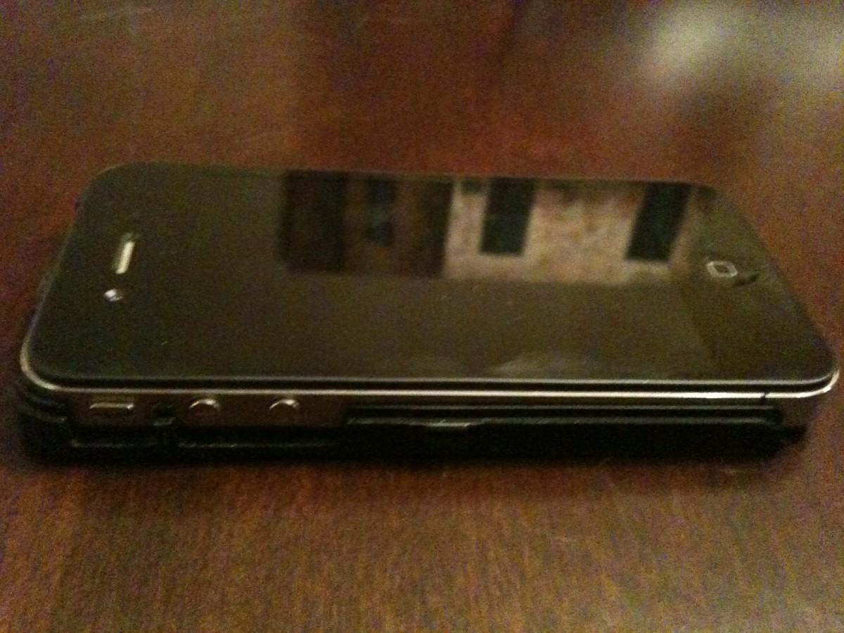 The iPhone 4 sitting in the back part of the OtterBox Defender series hard plastic case with the front part of the shell removed.