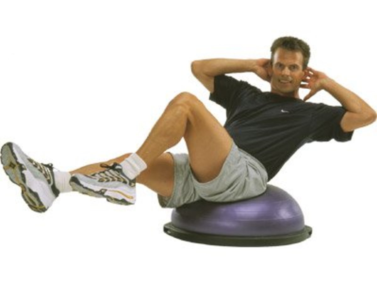 Man in black t-shirt and tan short performing sit-ups while sitting on top of a purple bosu balance ball