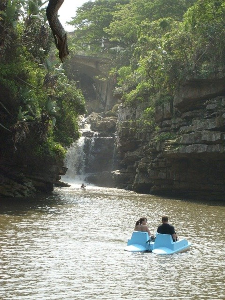 Serene Pedal Boat with two people on a blue pedal boat with Cliffs and trees on Both Sides