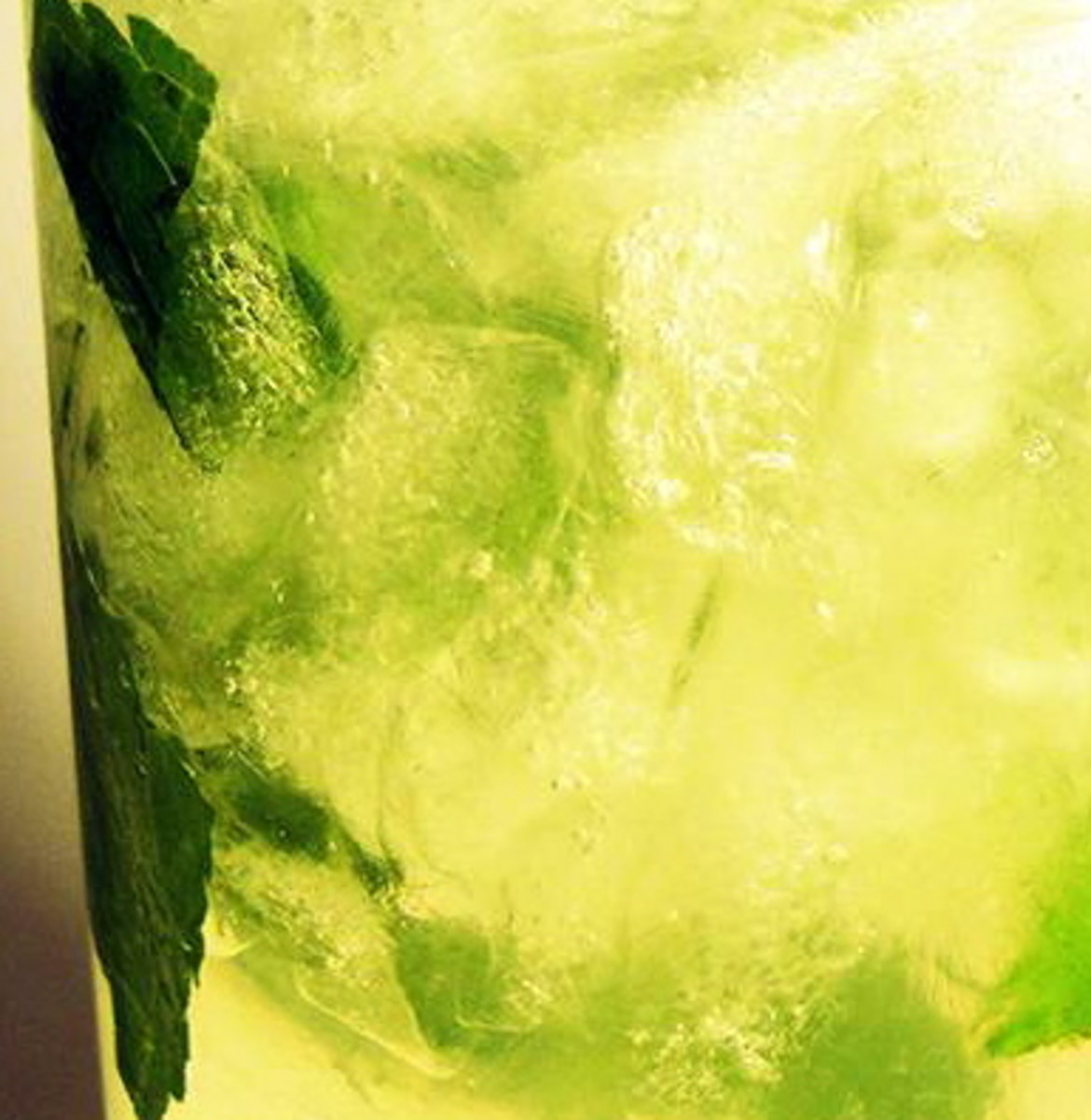 Gin over crushed ice with soda water, mint leaves and lime wedges