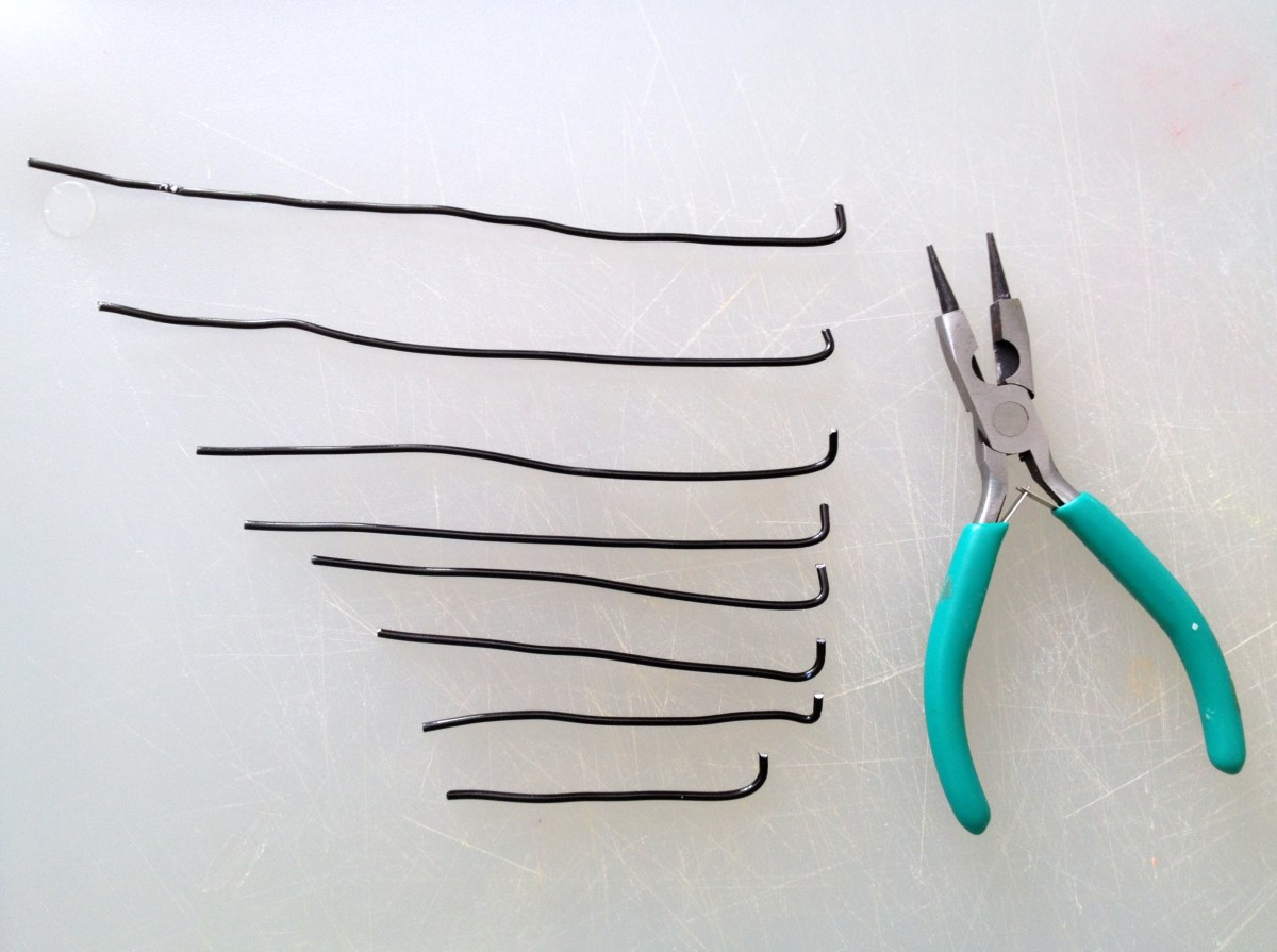 Use pliers to bend one end of each wire up so that it will support a clay planet.