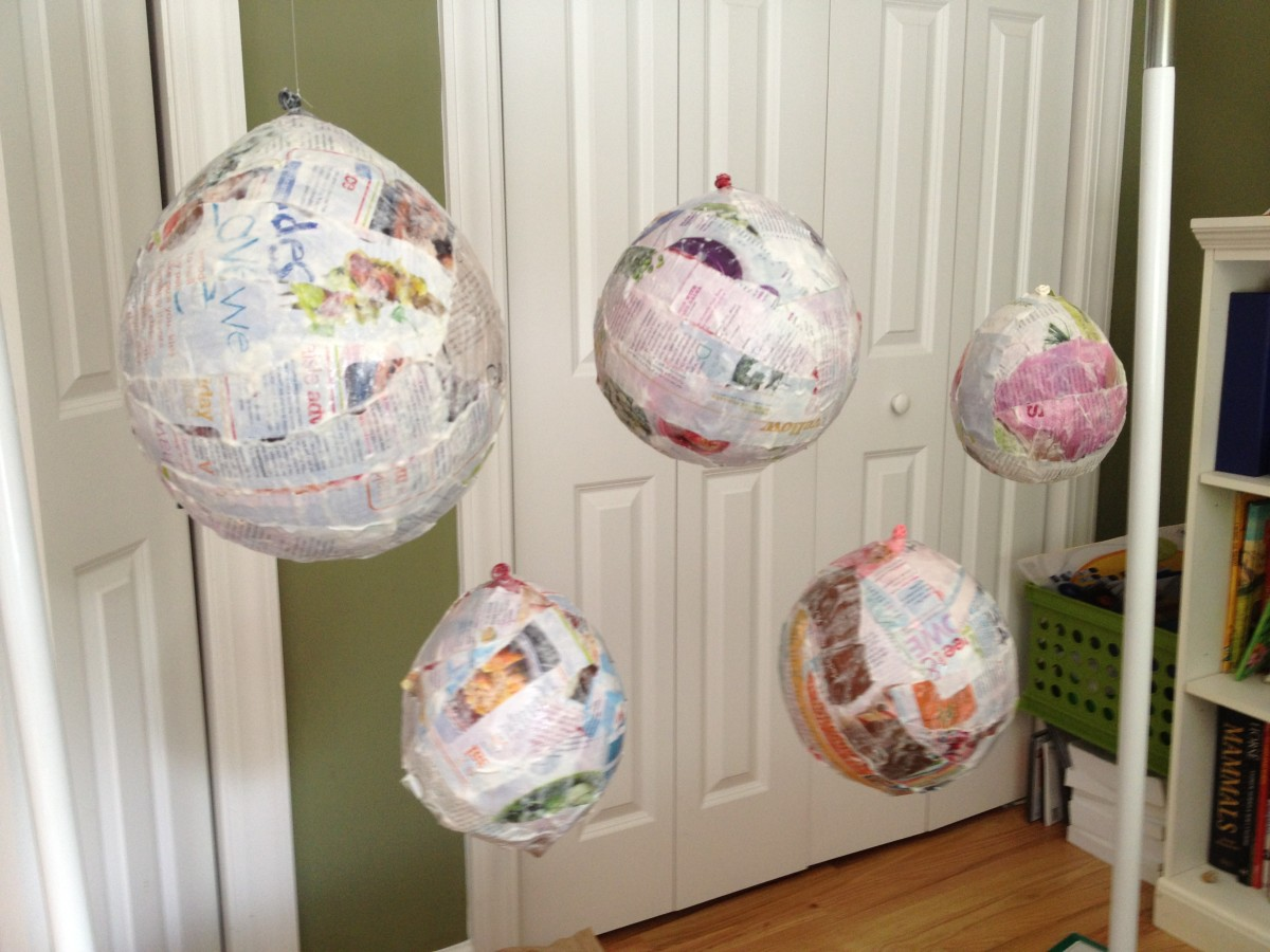 Hang paper mache planets to dry.  Protect the floor with newspaper or an old bed sheet.