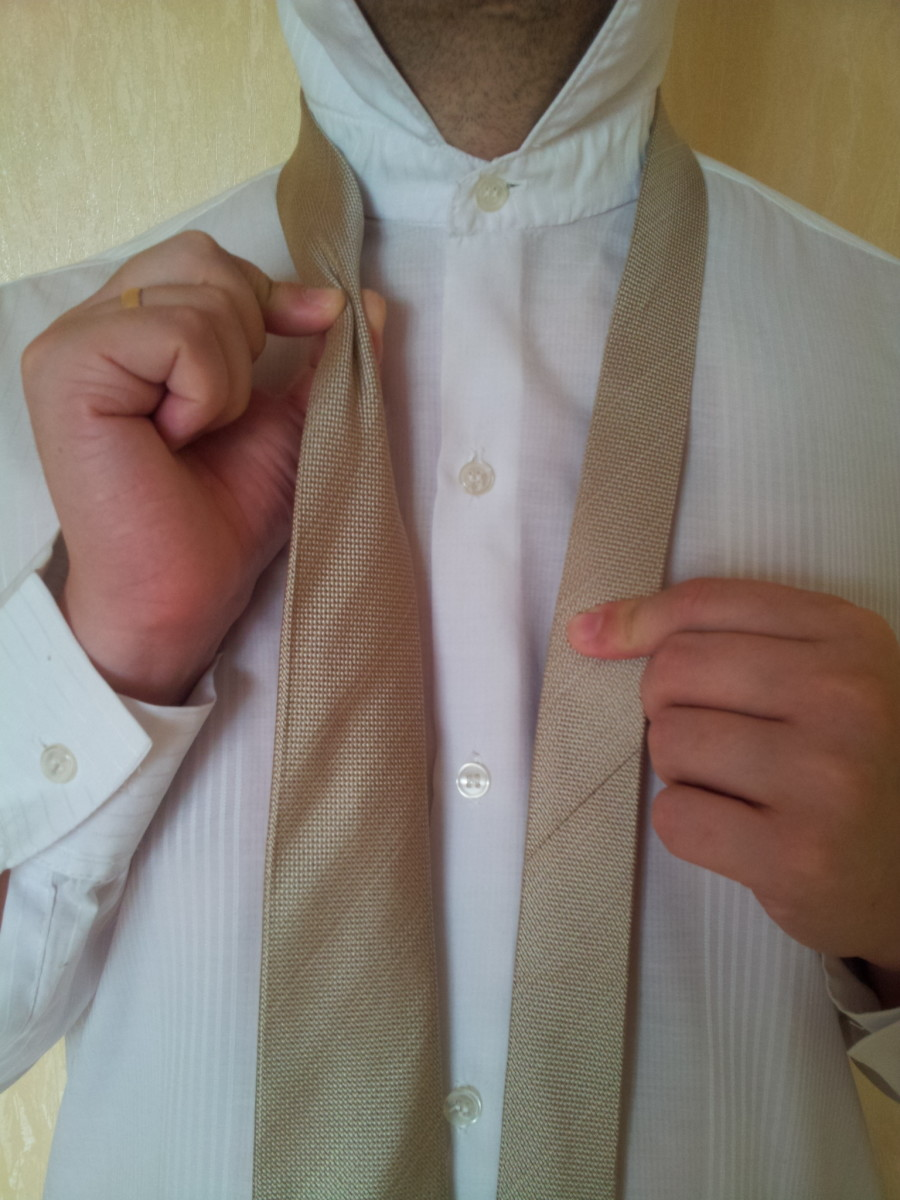 Step 2. Squeeze the tie at the neck and make a dimple.