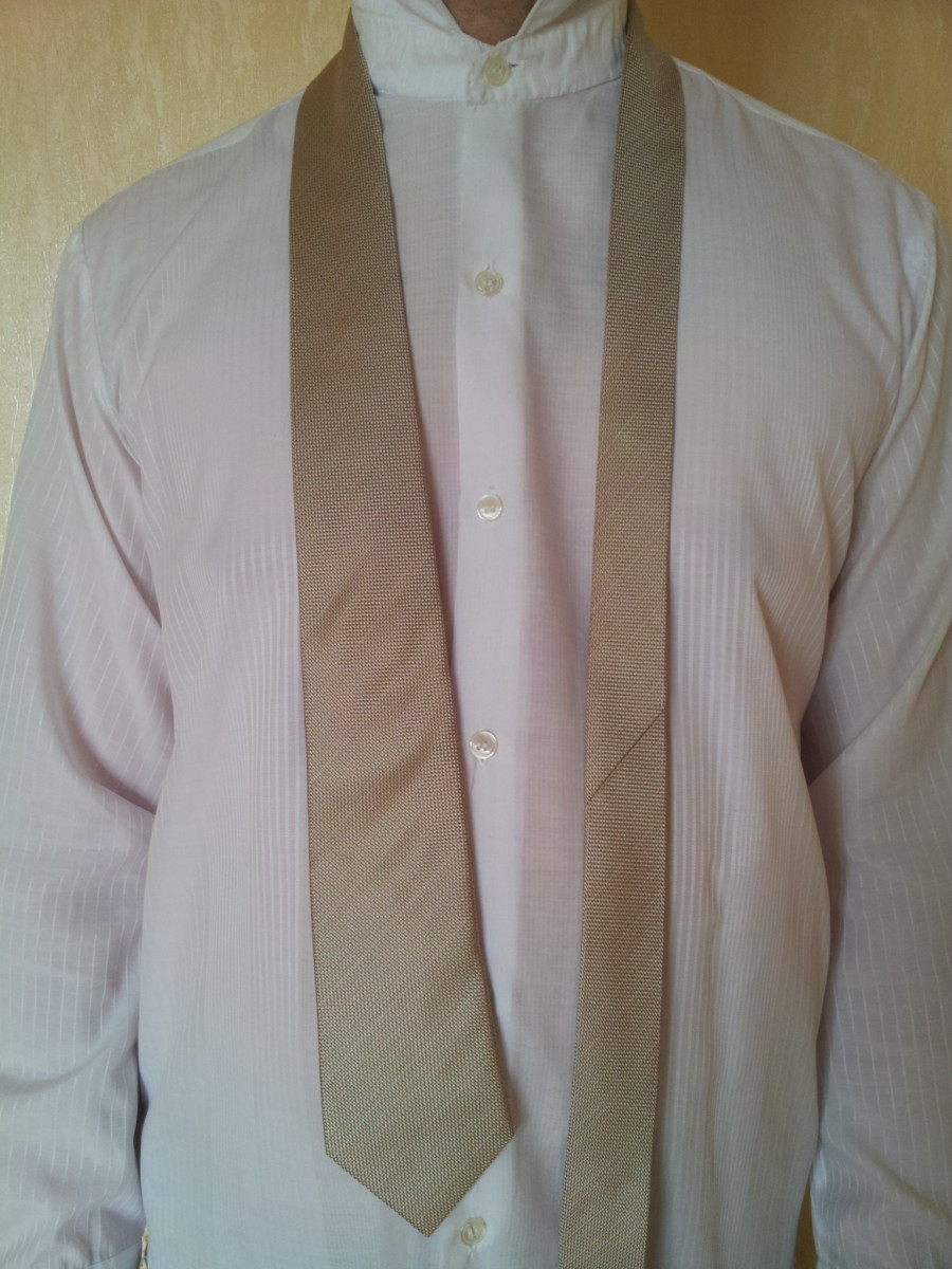 Step 1. Place the tie around your neck. Make sure that the wide end touches your belt in the middle.