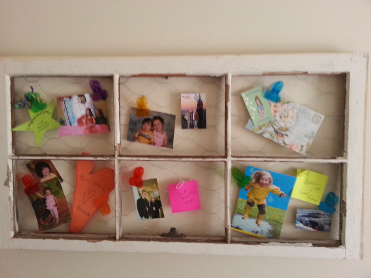 Old wood window without glass repurposed into a message / picture board with chicken wire.