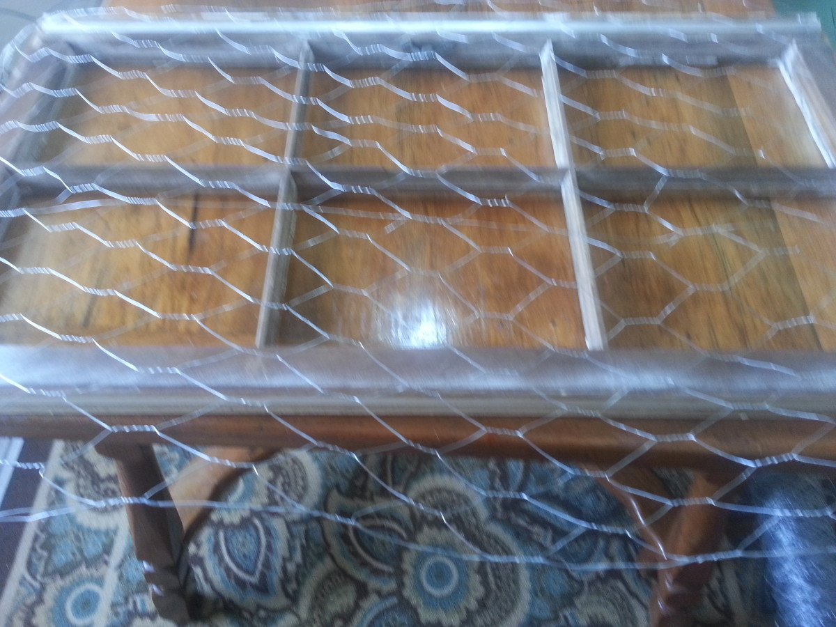Stapling chicken wire on back of old wood window without glass to make a message / picture board.