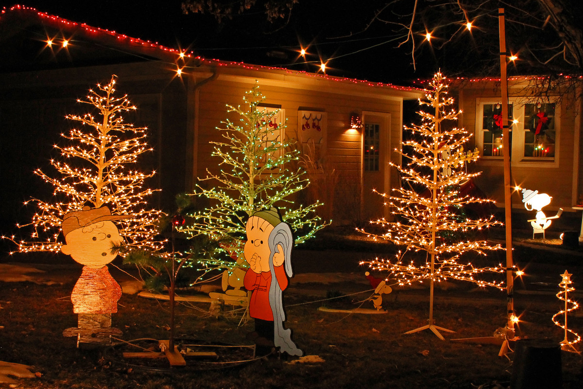 Charlie Brown and Linus stand in front of lighted trees. You can spot Snoopy playing hockey in the background.