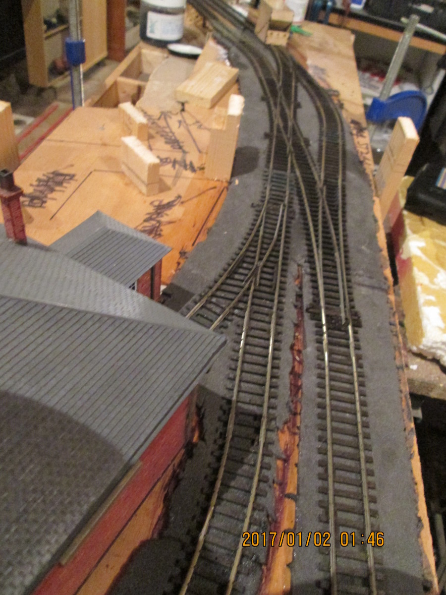 Trackwork adjusted by inserting a large radius Peco Streamline 'Y' point where the right-hand No.2 radius point was. Single slip reversed to ease passage of pick-up goods locomotive around its short train..