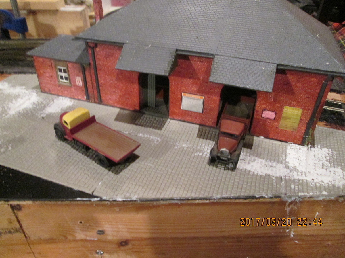 The goods shed's been secured in place, granite sets added to front. A connecting road needs to be laid in to the coal depot under the access road via a tunnel. Front 'bleeds off' the layout.