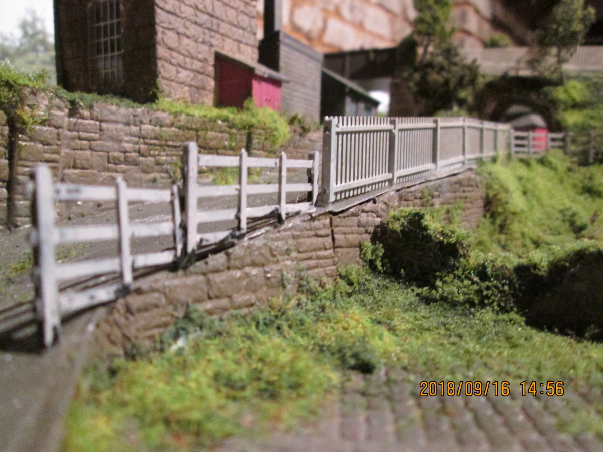 The ramp up from the coal depot has been given some white-painted safety fencing. The difference in fencing styles on the slope is to show the effects of the wartime blackout - drivers hitting the fence in the dark