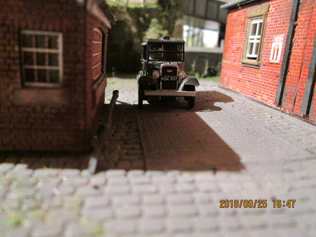 Taxi cab passes between goods shed and weigh office towards the road away