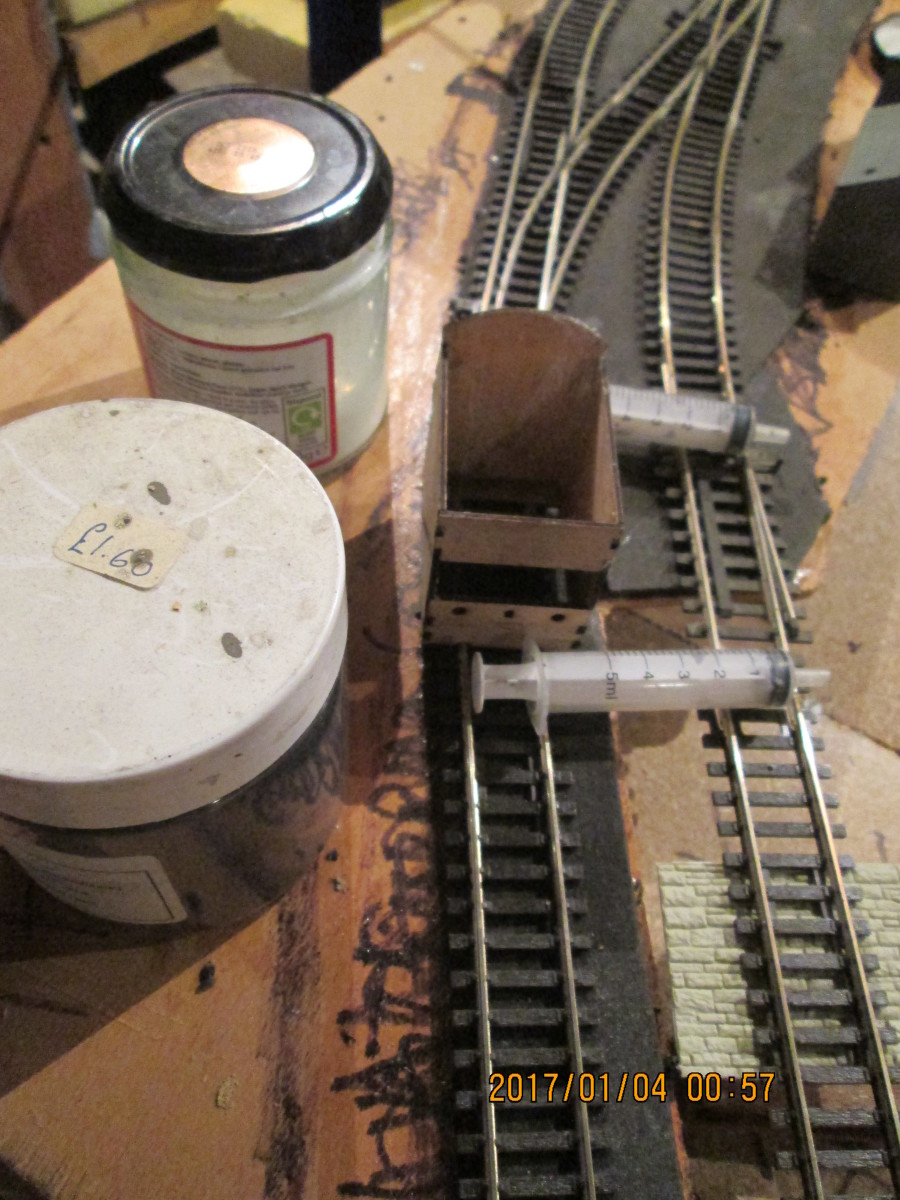 The tools for the ballasting job: large syringes suitable for pushing through dilated PVA/wood glue solution + washing-up liquid, jar of ballast (ash) and Poppy's Woodtech box with its 'chute' and lateral slot to allow an even flow of ballast
