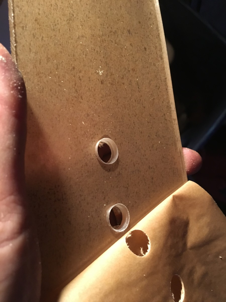 Two holes drilled into cast acrylic sheet with a step drill bit.