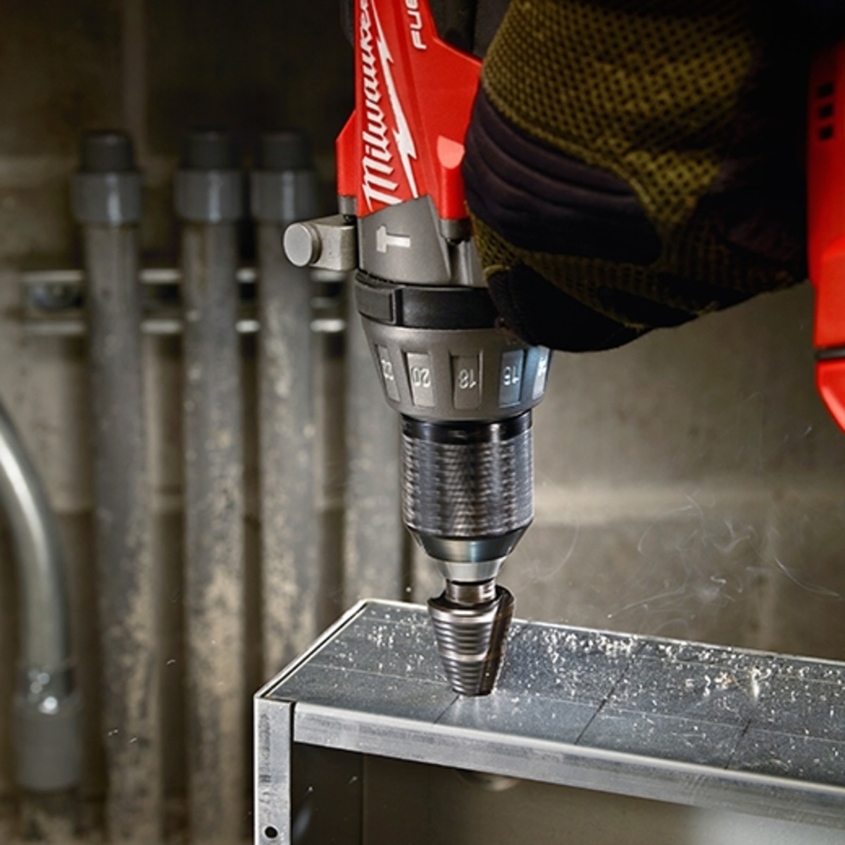 Step drill bit making large holes into a metal enclosure.