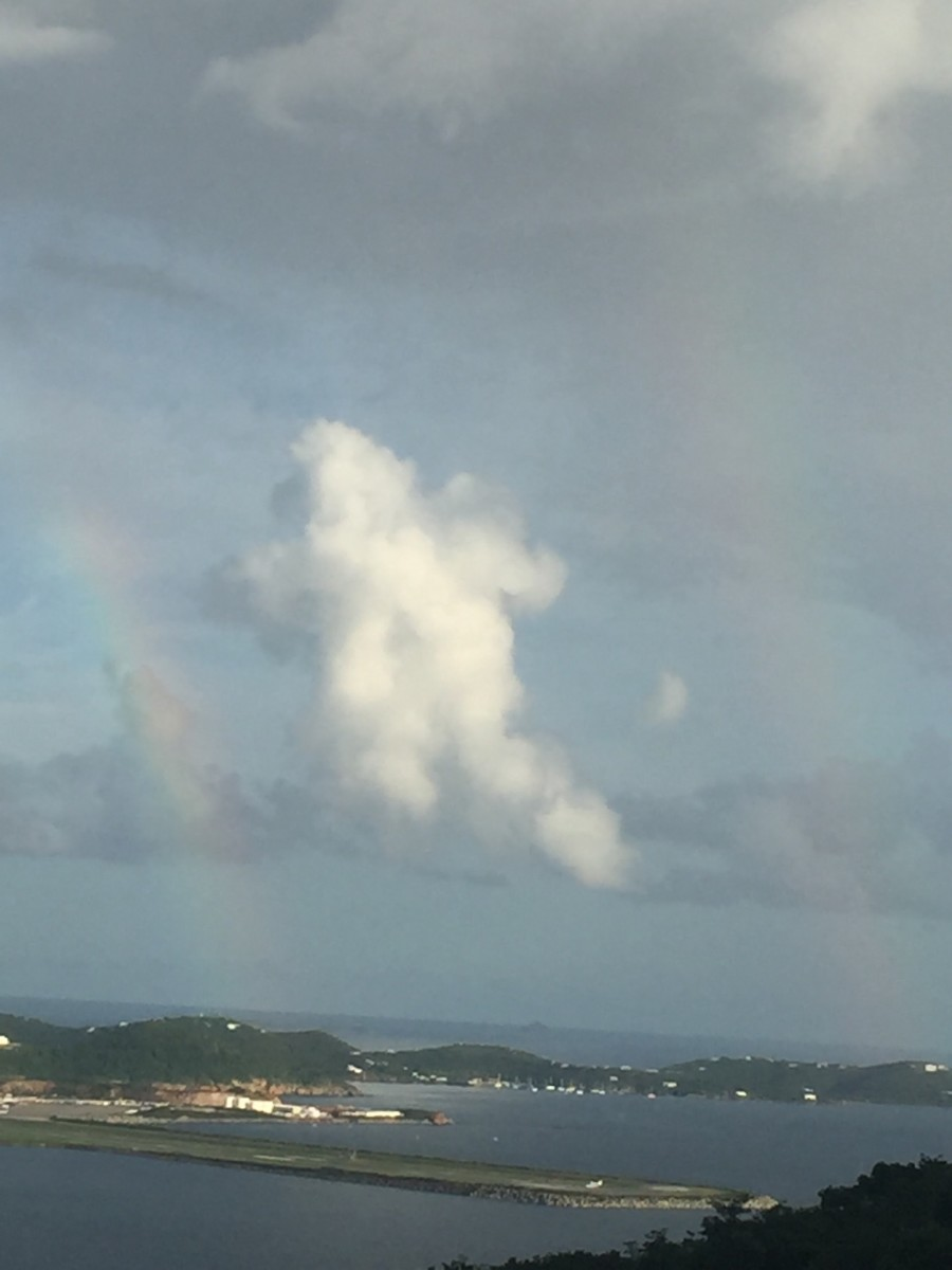 September 23, 2016 @ 5:20pm. St. Thomas USVI. This picture was taken over the Cyril R. King Airport. The caption is very interesting, It appears to be two rainbow with a cloud centered in a shape of a bear, perhaps or an angel.