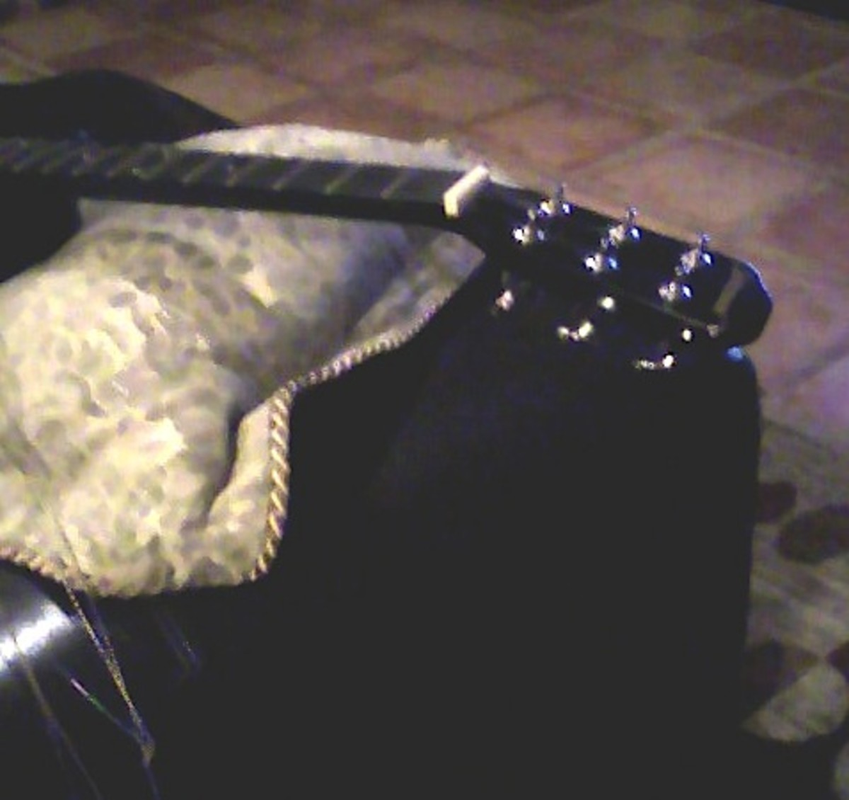 The strings off the neck; pillow propping up guitar.