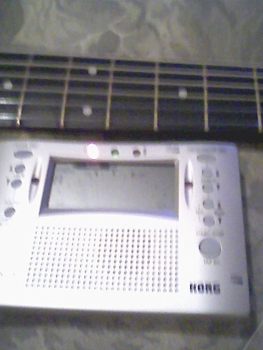 A chromatic tuner is a great help in tuning the guitar.  Here, the leftmost LED is illuminated, showing that the string is flat.