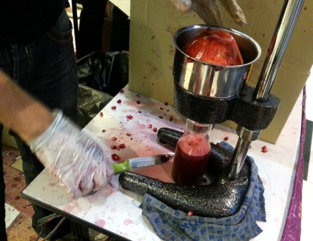 Juicing a pomegranate fruit, at a shop in Kuala Lumpur, Malaysia