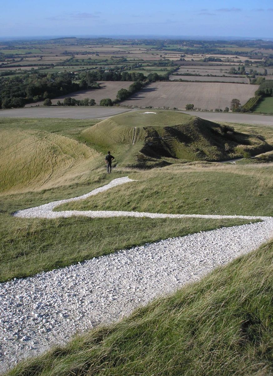 Closeup shot of a few chalk lines of the Uffington White Horse. Dragon Hill on the background.